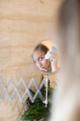 woman applying cream in mirror